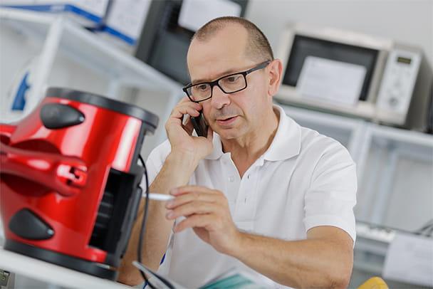 Ein Mann telefoniert während einer Reparatur eines Geräts in seiner Werkstatt im Firmenquartier